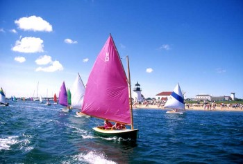 Sailboat with a pink sail with the Brant Point lightshous in the background